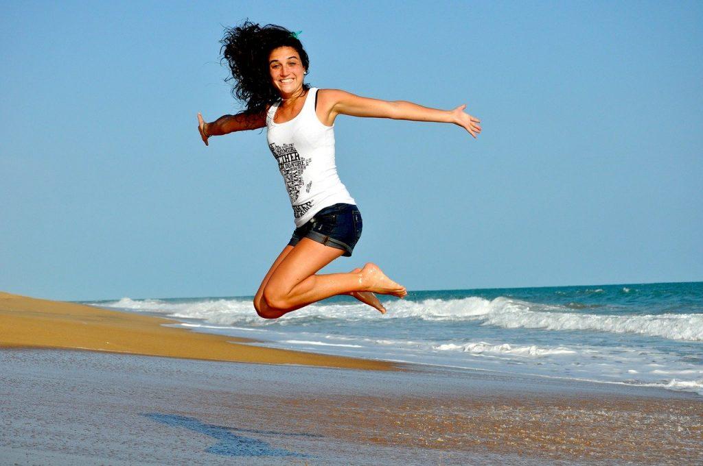 jeune femme souriante qui saute sur la plage