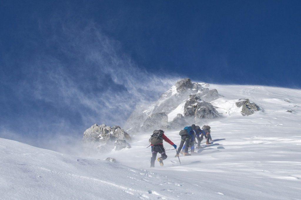personnes pratiquant l'alpinisme dans la neige