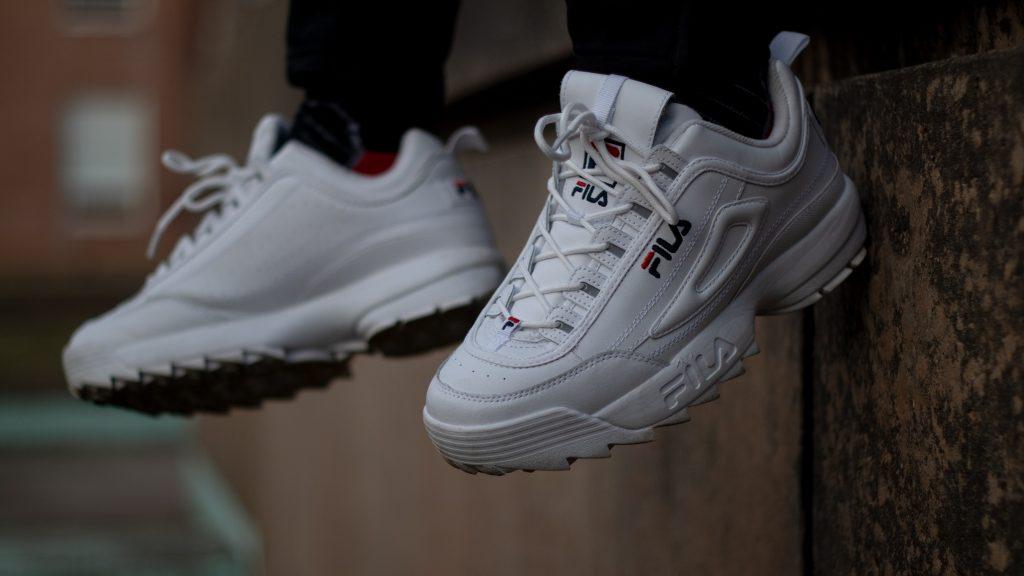 pieds d'une personne portant des baskets blanches