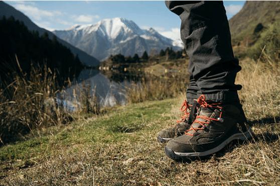 vue sur les pieds d'une personne qui porte des chaussures de randonnée à la montagne