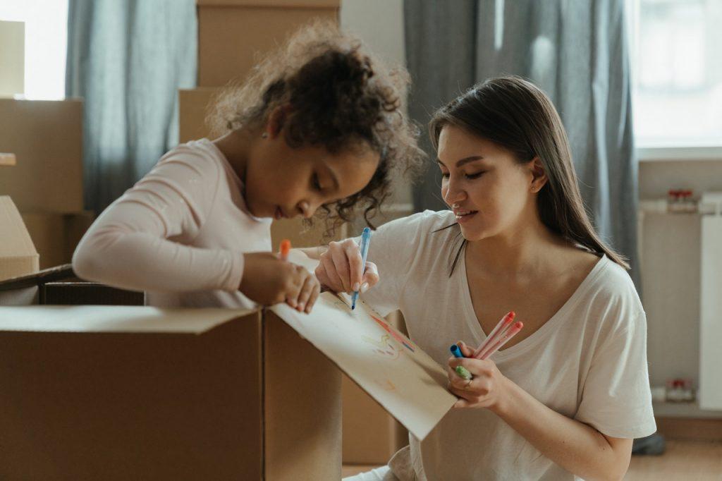 mère et sa fille qui dessine sur un carton de déménagement