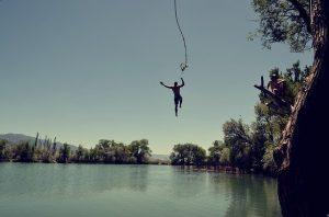 homme saute d'une corde au dessus de l'eau